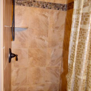 The Upstairs Bathroom at The Huntley features a River Rock Flooring - The Cove at Fairview Vacation Rentals - Asheville NC