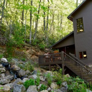 The Huntley front porch overlooks a waterfall - The Cove at Fairview Vacation Rentals - Asheville NC